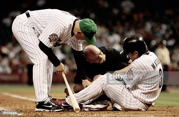 Kazuo Matsui of the Houston Astros is attended to by assisstant trainer Rex Jones and manager Brad Mills as he lays on the ground after hitting a...