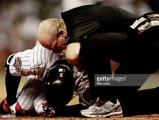 Kazuo Matsui of the Houston Astros is attended to by assisstant trainer Rex Jones as he lays on the ground after hitting a foul ball off his knee...