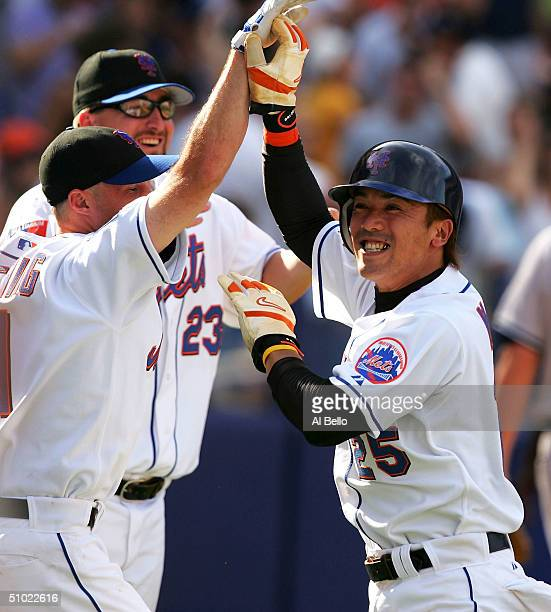 Kazuo Matsui of the New York Mets celebrates with Joe McEwing and Jason Phillips after scoring the winning run off of a Shane Spencer hit against the...