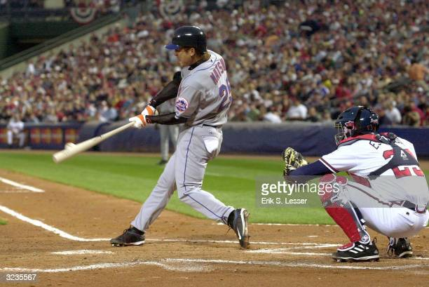 Kazuo Matsui of the New York Mets hits a double in the second inning off pitcher Russ Ortiz of the Atlanta Braves as catcher Johnny Estrada looks on...