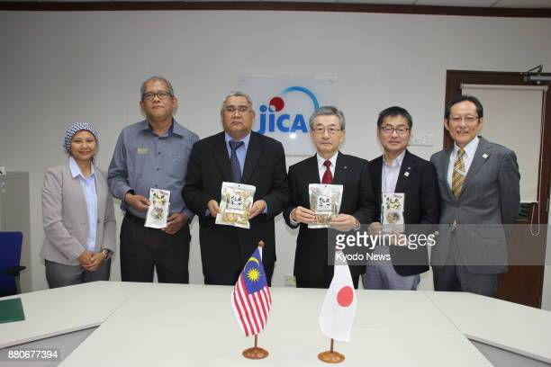 Kazuo Shionoya president of Japanese processed seafood maker Edoya Co and Mohd Rejab director of Malaysian food producer Jabi Rice Sdn Bhd pose with...