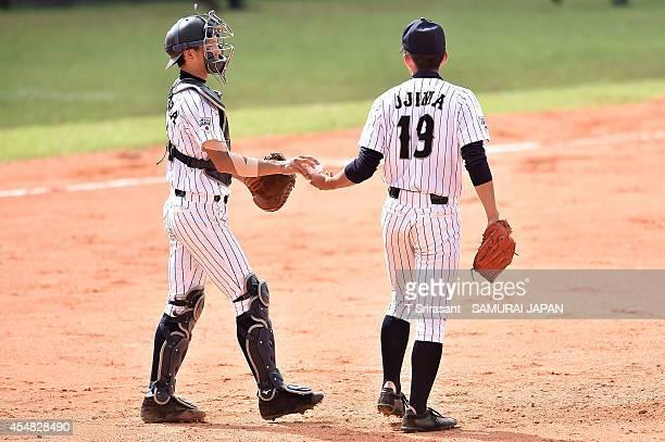 Kazuya Ojima of Japan gets ball from team mate Ryoya Kurihara during the Asian 18U Baseball Championship final game between Japan and South Korea at...