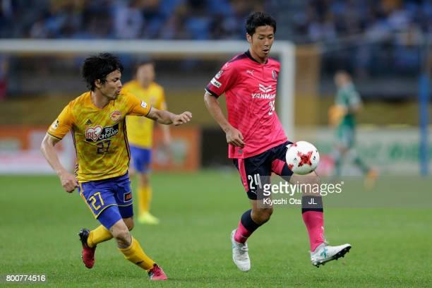 Kazuya Yamamura of Cerezo Osaka and Kazuki Oiwa of Vegalta Sendai compete for the ball during the J.League J1 match between Vegalta Sendai and Cerezo...