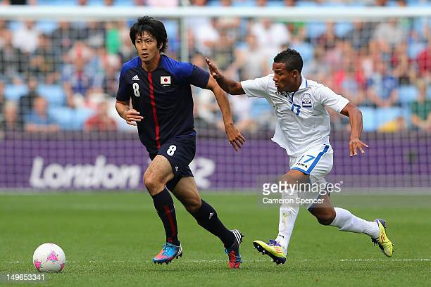 Kazuya Yamamura of Japan contols the ball ahead of Luis Garrido of Honduras during the Men's Football first round Group D Match between Japan and...
