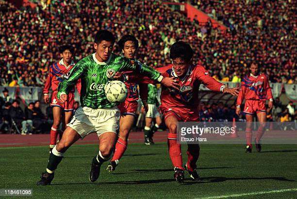 Kazuyoshi Miura of Verdy Kawasaki and Eiji Gaya of Kashima Antlers compete for the ball during the Suntory Championship first leg match between...
