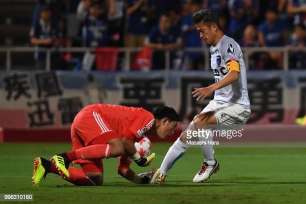 Kazuyoshi Miura of Yokohama FC and Hiroki Iikura of Yokohama FMarinos compete for the ball during the Emperor's Cup third round match between...