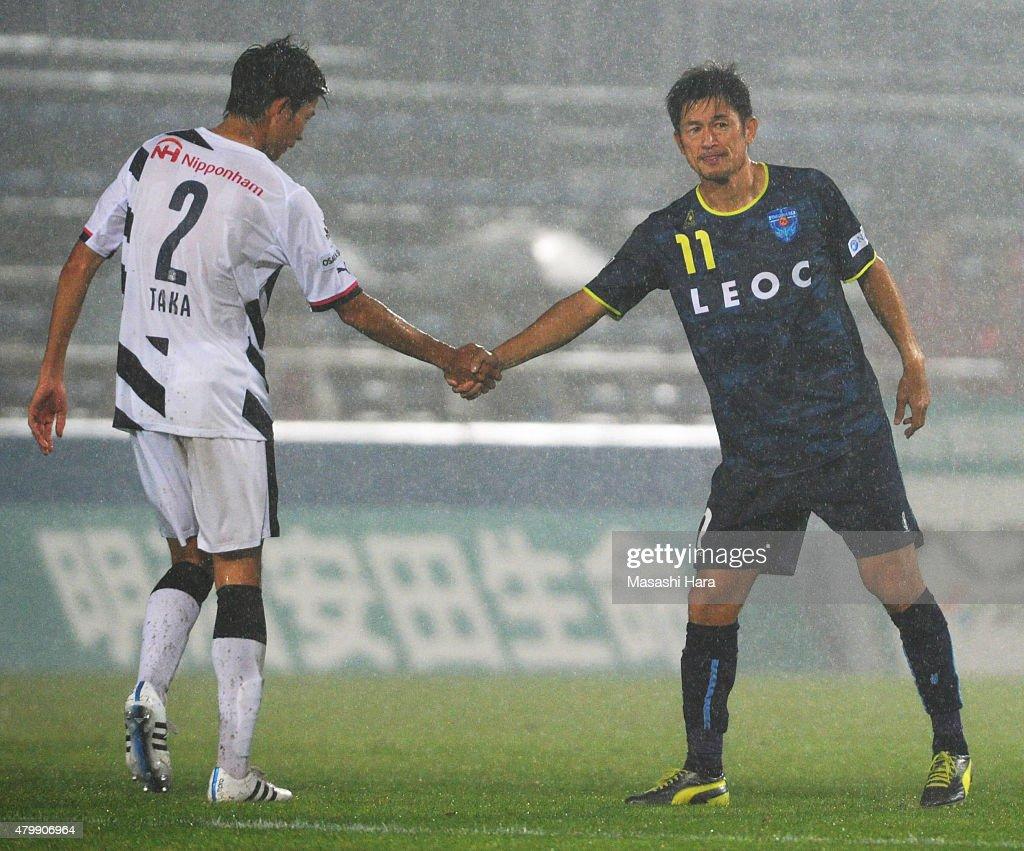 Kazuyoshi Miura #11 of Yokohama FC shake hands with Takahiro Ogihara during the J.League second division match between Yokohama FC and Cerezo Osaka at Nippatsu Mitsuzawa Stadium on July 8, 2015 in Yokohama, Kanagawa, Japan.