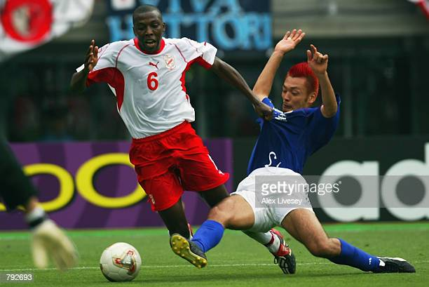 Kazuyuki Toda of Japan tackles Hatem Trabelsi of Tunisia in the penalty area during the FIFA World Cup Finals 2002 Group H match played at the...