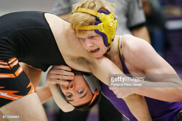 Keagan Rice of Cheverus right competes with Josiah Garcia of Biddeford in the 145lb class during the Class A South wrestling regional finals at...