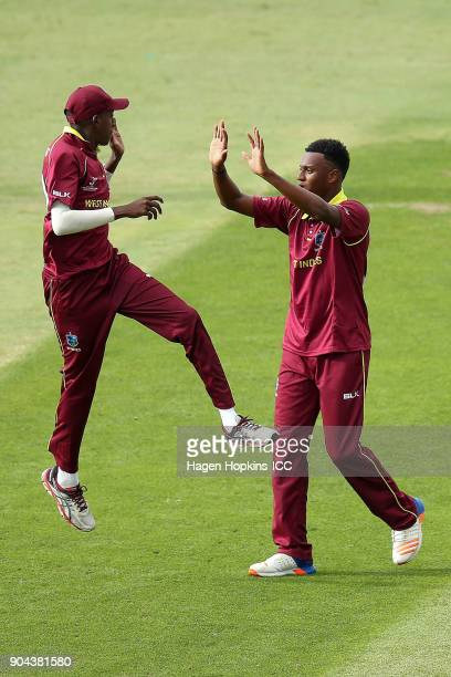 Keagan Simmons and Ronaldo Alimohamed of the West Indies celebrates after taking the wicket of Rachin Ravindra of New Zealand during the ICC U19...