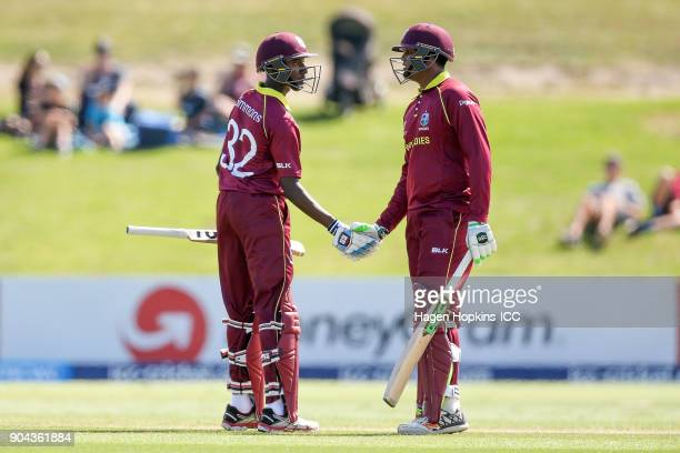 Keagan Simmons of the West Indies celebrates his half century with teammate Bhaskar Yadram during the ICC U19 Cricket World Cup match between New...