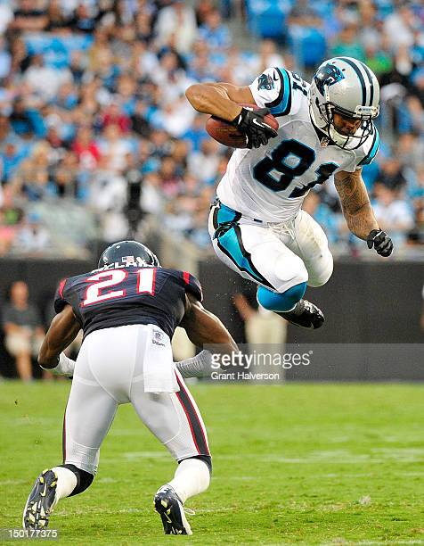 Kealoha Pilares of the Carolina Panthers hurdles Brice McCain of the Houston Texans during a preseason game at Bank of America Stadium on August 11...