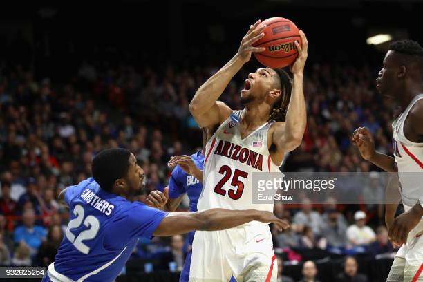 Keanu Pinder of the Arizona Wildcats handles the ball against Dontay Caruthers of the Buffalo Bulls during the first round of the 2018 NCAA Men's...
