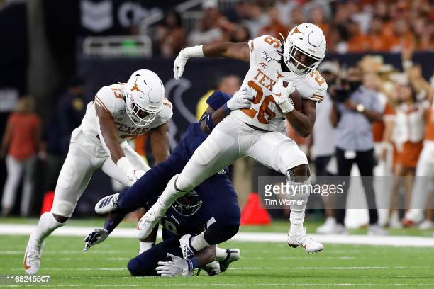 Keaontay Ingram of the Texas Longhorns breaks a tackle by Dasharm Newsome of the Rice Owls in the first half at NRG Stadium on September 14 2019 in...