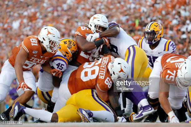 Keaontay Ingram of the Texas Longhorns is stopped short of the goal line by Michael Divinity Jr. #45 of the LSU Tigers and Patrick Queen in the first...