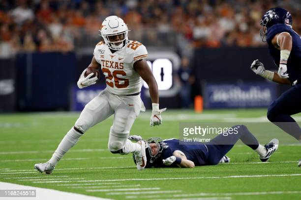 Keaontay Ingram of the Texas Longhorns runs the ball past Dylan Silcox of the Rice Owls in the first half at NRG Stadium on September 14, 2019 in...