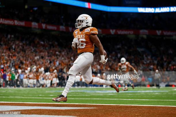 Keaontay Ingram of the Texas Longhorns rushes for a touchdown in the fourth quarter against the Utah Utes during the Valero Alamo Bowl at the...