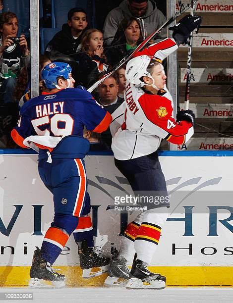 Keaton Ellerby of the Florida Panthers has his helmet jarred loose on a body check by Michael Haley of the New York Islanders during the third period...