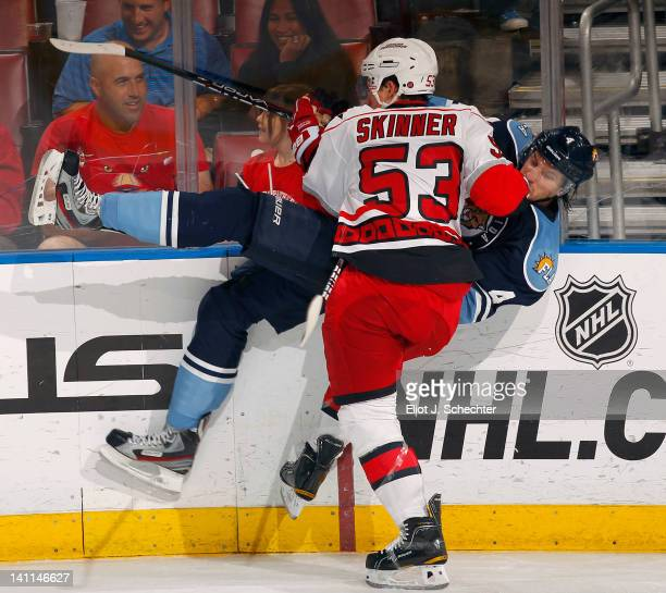 Keaton Ellerby of the Florida Panthers is checked into the boards by Jeff Skinner of the Carolina Hurricanes at the BankAtlantic Center on March 11...