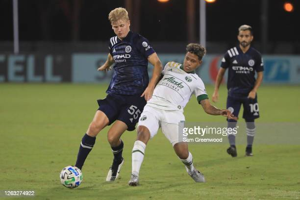 Keaton Parks of New York City fights for the ball with Andy Polo of Portland Timbers during a quarter final match of MLS Is Back Tournament between...