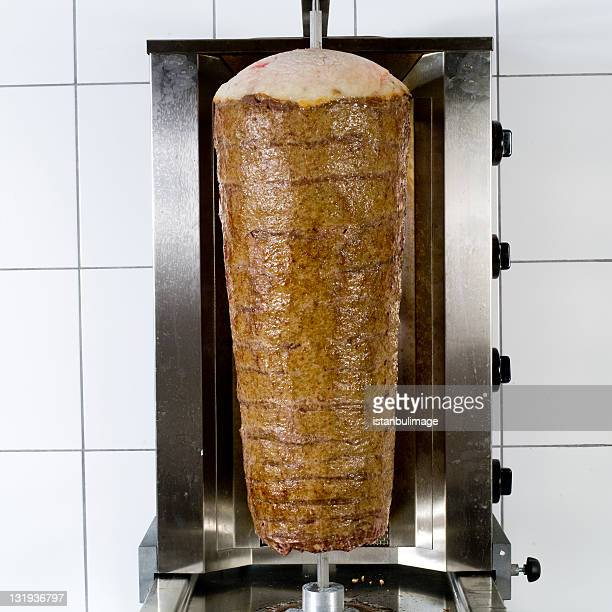 Kebab on a rod with a white tile background