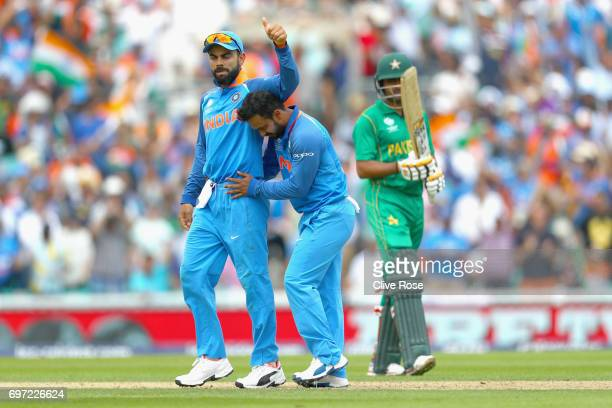 Kedar Jadhav of India celebrates the wicket of Babar Azam of Pakistan with Virat Kohli during the ICC Champions trophy cricket match between India...