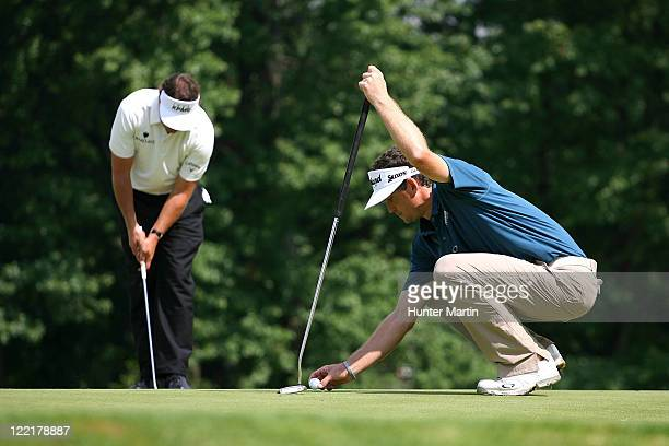 Keegan Bradley and Phil Mickelson line up putts on the 18th green during round two of The Barclays at Plainfield Country Club on August 26 2011 in...