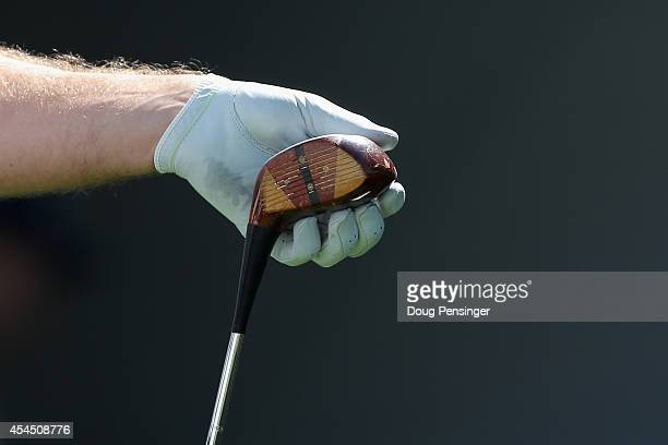 Keegan Bradley examines a vintage persimmon wood driver to hit a tee shot on the first hole during practice ahead of the BMW Championship at the...