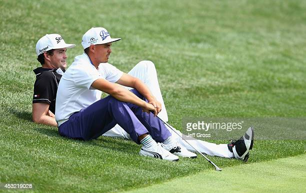 Keegan Bradley of the United States and Rickie Fowler of the United States sit on the edge of a green during a practice round prior to the start of...