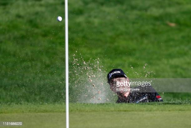 Keegan Bradley, of the United States, hits from the green side bunker on 18 during the Final Round of the Travelers Championship on June 23, 2019 at...