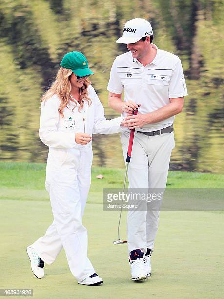 Keegan Bradley of the United States smiles alongside caddie and girlfriend Jillian Stacey during the Par 3 Contest prior to the start of the 2015...