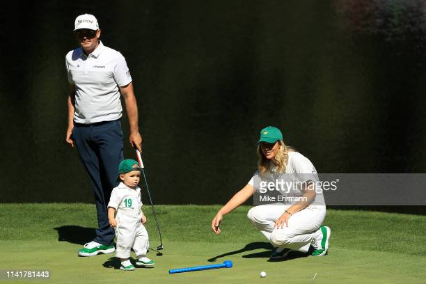 Keegan Bradley of the United States stands a green with his wife Jillian Stacey and son Logan James during the Par 3 Contest prior to the Masters at...
