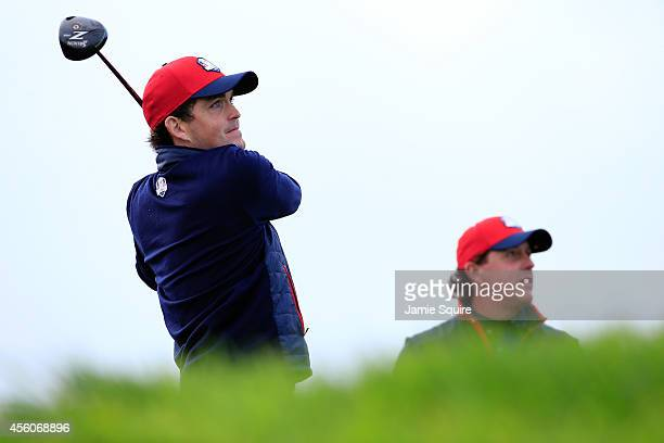 Keegan Bradley of the United States tees off as Phil Mickelson of the United States looks on during practice ahead of the 2014 Ryder Cup on the PGA...