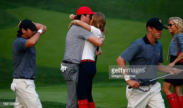 Keegan Bradley of the US Team hugs his girlfriend Jillian Stacey on the 15th green after the team of Mickelson/Bradley defeated the Day/DeLaet team...
