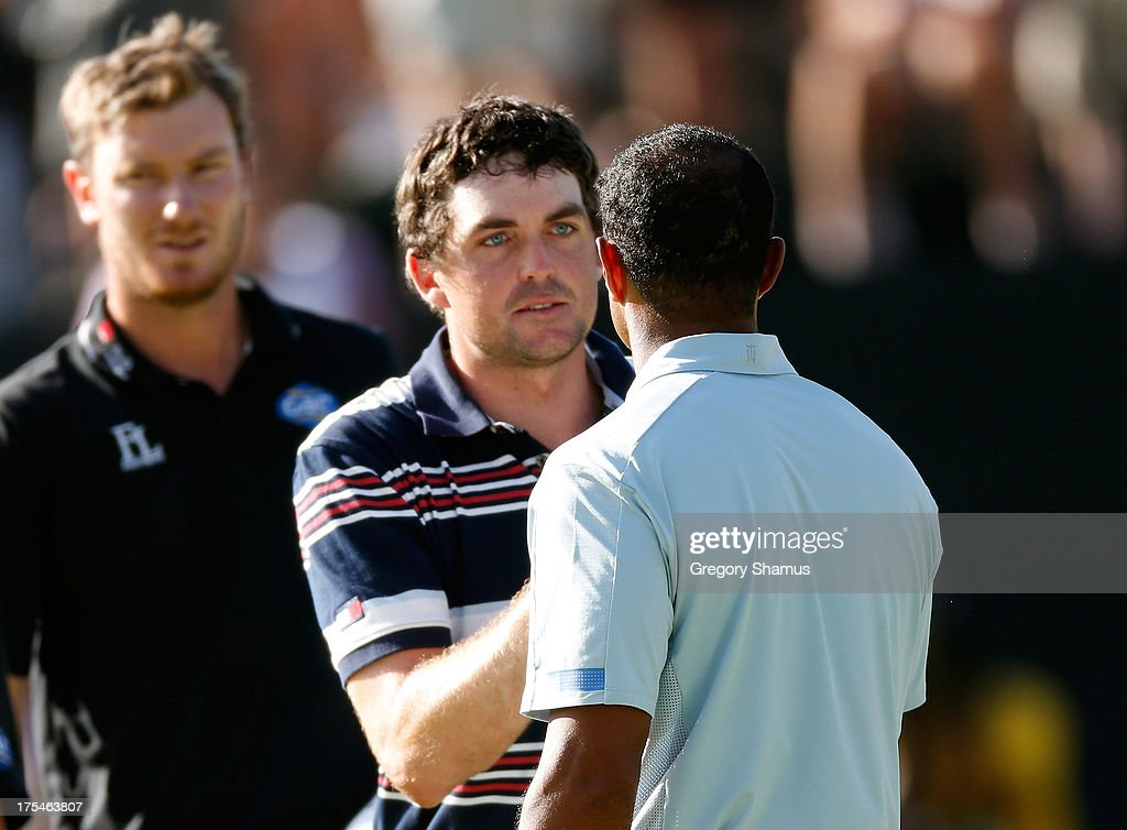 Keegan Bradley (C) shakes hands with Tiger Woods (R) as Chris Wood of England looks on after finishing the Third Round of the World Golf Championships-Bridgestone Invitational at Firestone Country Club South Course on August 3, 2013 in Akron, Ohio.