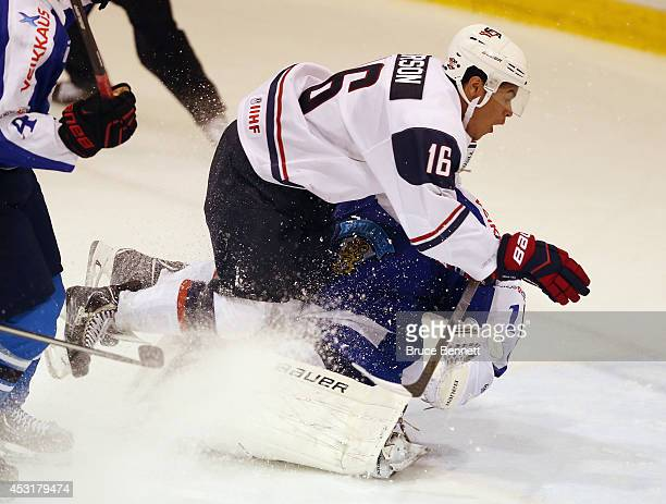 Keegan Iverson of USA White takes a charging penalty on goaltender Juuse Saros of Team Finland during the 2014 USA Hockey Junior Evaluation Camp at...