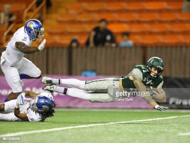 Keelan Ewaliko of the Hawaii Rainbow Warriors is taken down short of the end zone after being tripped up by Andre Chachere of the San Jose State...