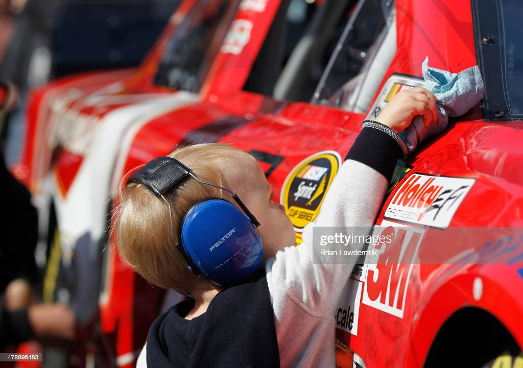 Keelan Harvick, son of Kevin Harvick, driver of the #4 Budweiser Chevrolet, cleans off his father's car during practice for the NASCAR Sprint Cup Series Food City 500 at Bristol Motor Speedway on March 15, 2014 in Bristol, Tennessee.