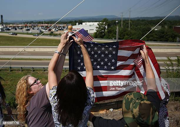 Keely Farris and others hang an American flag as they join with the others from MillerMotte Technical College for a moment of reflection on their...
