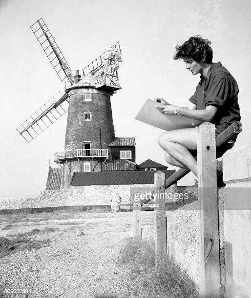 A keen amateur painter holidaymaker Rowena Ryle of Cambridge sketches the Cley Windmill at Cley next the Sea near Blakeney Point on the north coast...