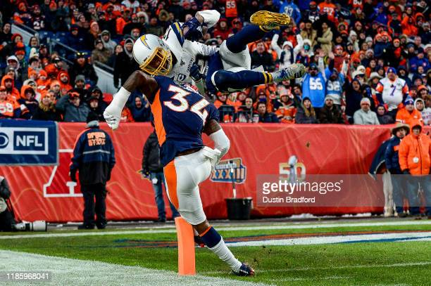 Keenan Allen of the Los Angeles Chargers leaps over Will Parks of the Denver Broncos to score a third quarter touchdown on a reception at Empower...