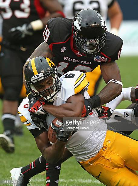 Keenan Davis of the Iowa Hawkeyes is brought down by Demetrius Stone of the Northern Illinois Huskies at Soldier Field on September 1 2012 in Chicago...