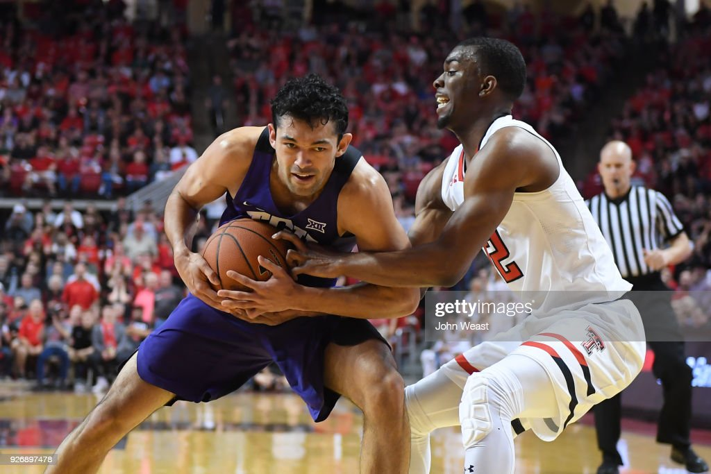 Keenan Evans #12 of the Texas Tech Red Raiders and Alex Robinson #25 of the TCU Horned Frogs struggle for the ball during the second half of the game on March 3, 2018 at United Supermarket Arena in Lubbock, Texas. Texas Tech defeated TCU