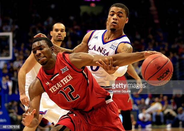 Keenan Evans of the Texas Tech Red Raiders controls the ball as Frank Mason III of the Kansas Jayhawks defends during the game at Allen Fieldhouse on...