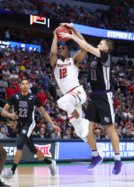 Keenan Evans of the Texas Tech Red Raiders drives in for a shot against Ivan Canete of the Stephen F Austin Lumberjacks in the second half in the...