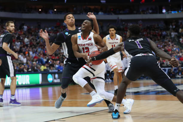 Keenan Evans of the Texas Tech Red Raiders drives to the basket against TJ Holyfield and Kevon Harris of the Stephen F Austin Lumberjacks in the...