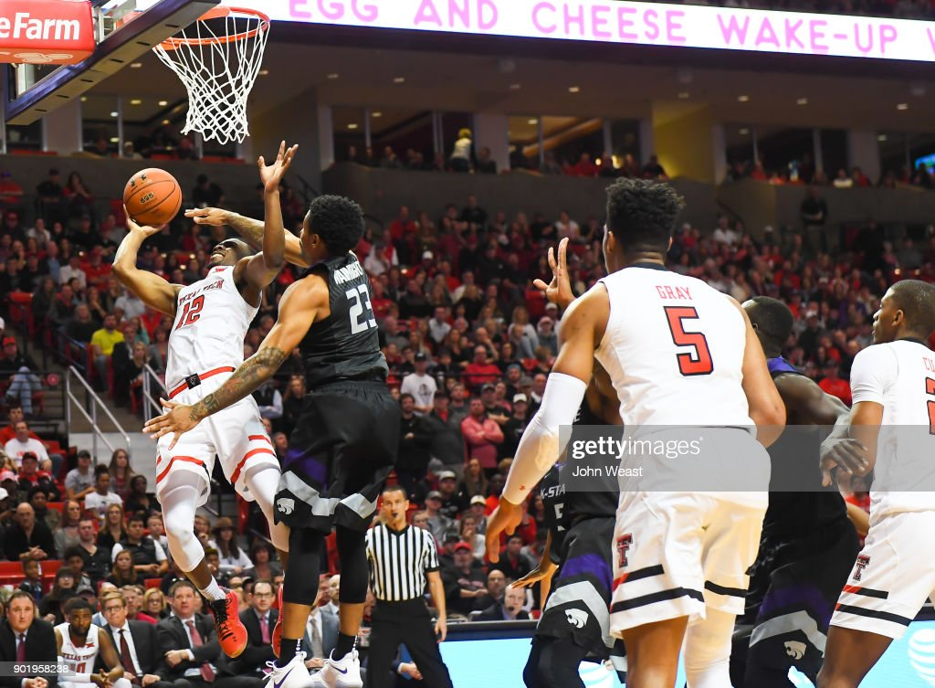 Keenan Evans #12 of the Texas Tech Red Raiders goes to the basket and is fouled by Amaad Wainright #23 of the Kansas State Wildcats during the game on January 6, 2018 at United Supermarket Arena in Lubbock, Texas. Texas Tech won the game 74-58.