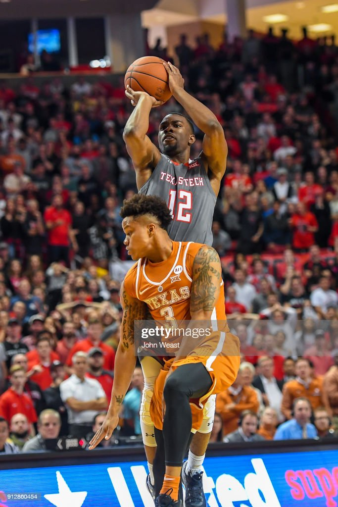 Keenan Evans #12 of the Texas Tech Red Raiders is fouled while shooting by Jacob Young #3 of the Texas Longhorns during the game on January 31, 2018 at United Supermarket Arena in Lubbock, Texas. Texas Tech defeated Texas 73-71 in overtime.