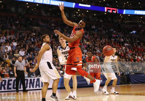 Keenan Evans of the Texas Tech Red Raiders loses the ball as he drives to the basket against PJ Thompson and Matt Haarms of the Purdue Boilermakers...