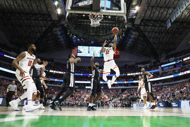 Keenan Evans of the Texas Tech Red Raiders shoots against Kevon Harris and Shannon Bogues of the Stephen F Austin Lumberjacks in the second half in...
